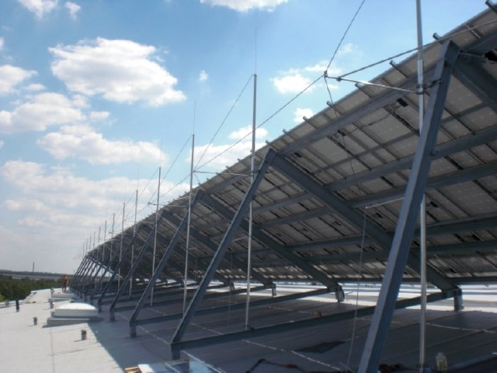 Fot.2a. Przykładowe rozwiązania ochrony odgromowej kolektorów fotowoltaicznych na dachach płaskich: a) wykorzystanie izolacyjnych elementów dystansujących, b) wykorzystanie przewodów o izolacji wysokonapięciowej [10]
